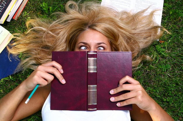 Giovane studente attraente che legge il libro