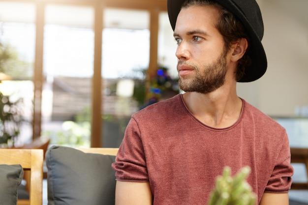 Giovane studente barbuto attraente serio o triste che porta cappello nero d'avanguardia che si siede da solo alla caffetteria spaziosa moderna
