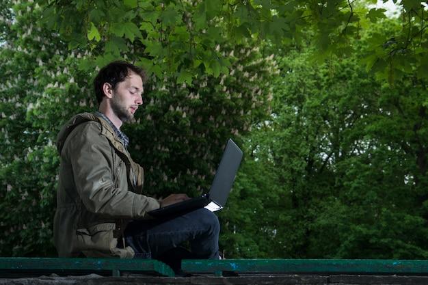 Giovane studente bello che si siede su una panchina di legno nel parco con il computer portatile