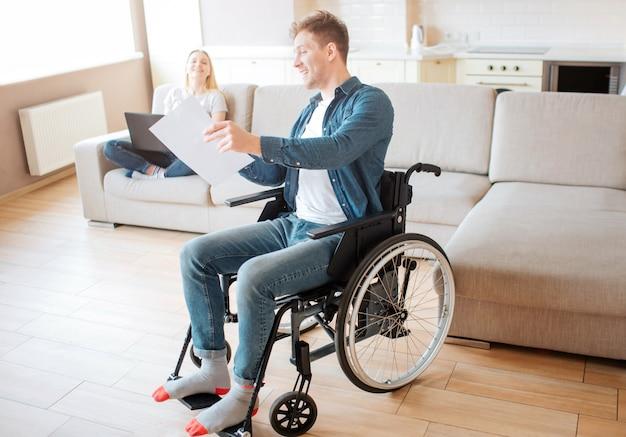 Giovane studente con sedia a rotelle che mostra pezzo di carta alla donna