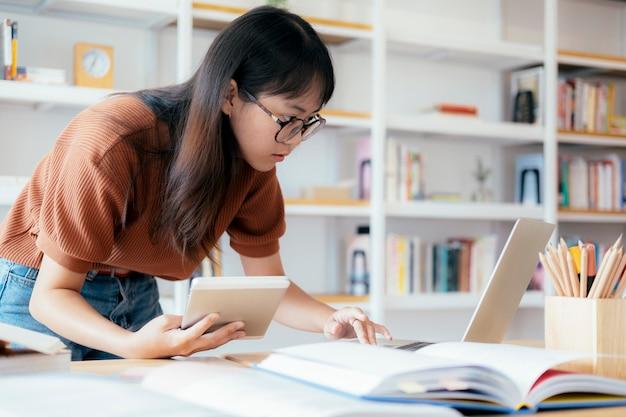 Giovane studente del collage che per mezzo del computer e del dispositivo mobile che studiano online.