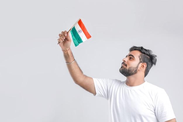 Giovane studente di college indiano che esamina bandiera indiana.