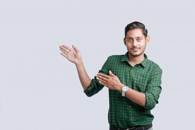 Giovane studente di college indiano che mostra direzione