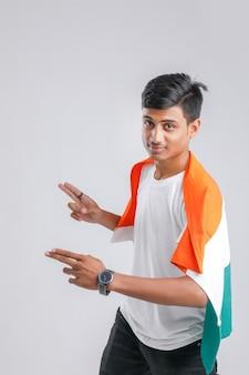 Giovane studente di college indiano in posa con bandiera indiana.
