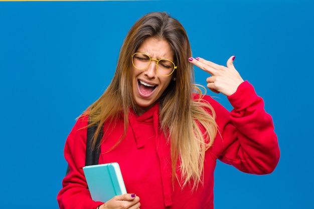 Giovane studente grazioso che sembra infelice e sollecitato, gesto di suicidio che fa il segno della pistola con la mano, indicante la testa