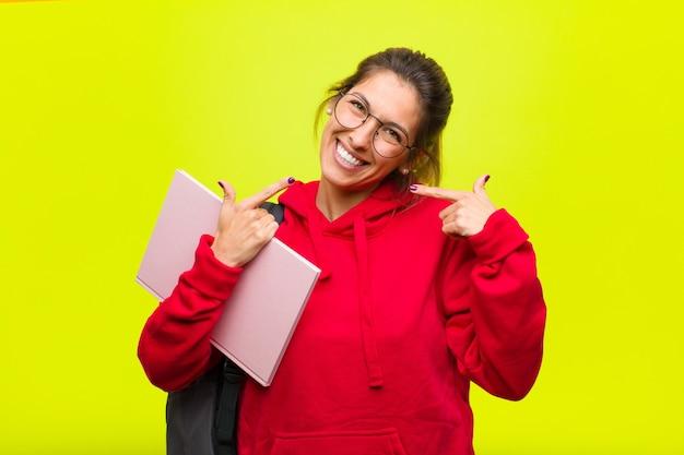Giovane studente grazioso che sorride con confidenza indicando il proprio ampio sorriso, atteggiamento positivo, rilassato, soddisfatto