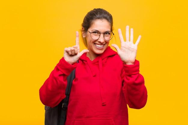 Giovane studente grazioso che sorride e che sembra amichevole, mostrando numero sette o settimo con la mano in avanti, conto alla rovescia