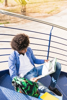 Giovane studente maschio africano che si siede sulla scala che legge il libro