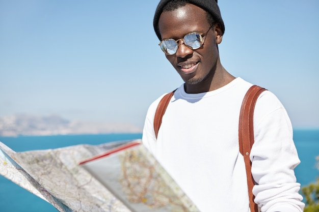 Giovane studente maschio afroamericano allegro in occhiali da sole con lenti a specchio alla ricerca di nuovi luoghi e punti di riferimento da visitare sulla mappa cartacea nelle sue mani durante un viaggio all'estero durante le vacanze estive