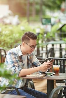 Giovane studente maschio asiatico che si siede al caffè della via e che per mezzo dello smartphone