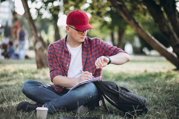Giovane studente maschio che lavora ad un computer in parco