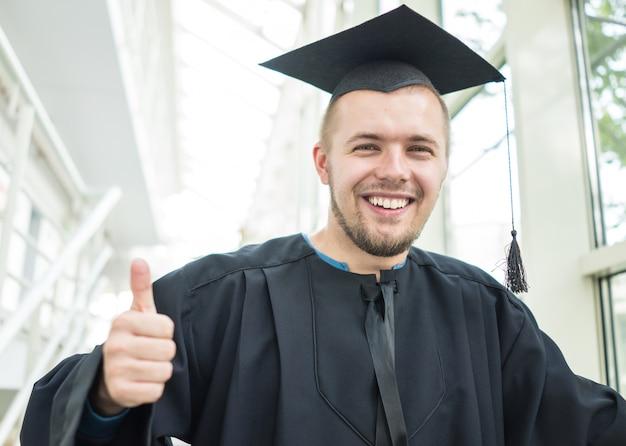 Giovane studente maschio in abito nero laurea