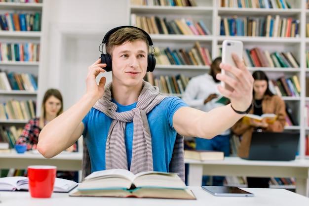 Giovane studente ragazzo bello sorridente seduto al tavolo nella biblioteca del college, ascoltando musica piacevole in cuffia