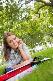 Giovane studente sorridente sdraiato sull'erba al telefono
