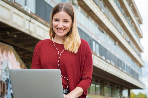 Giovane studente usando il portatile all'aperto.