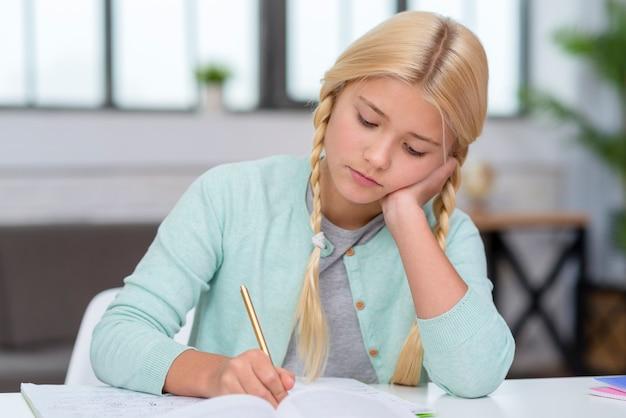 Giovane studentessa bionda che sembra annoiata e che scrive