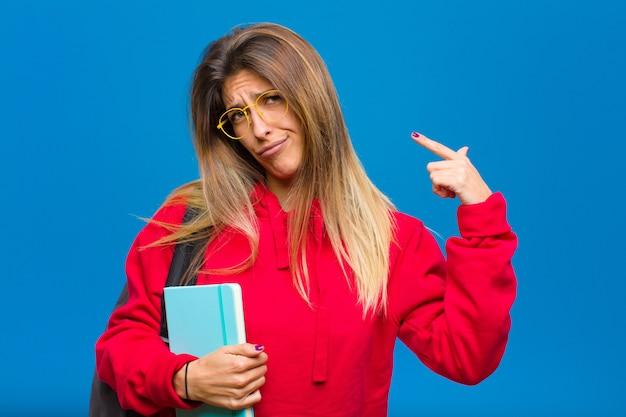 Giovane studentessa carina con un atteggiamento negativo che sembra orgogliosa e aggressiva, che punta verso l'alto o che fa segno divertente con le mani