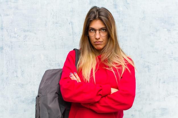 Giovane studentessa carina sentendosi dispiaciuta e delusa, sembrando seria, seccata e arrabbiata con le braccia incrociate