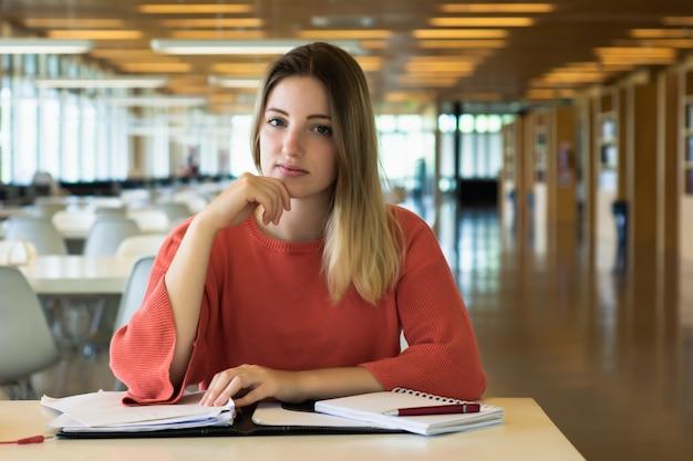 Giovane studentessa che studia nella biblioteca.