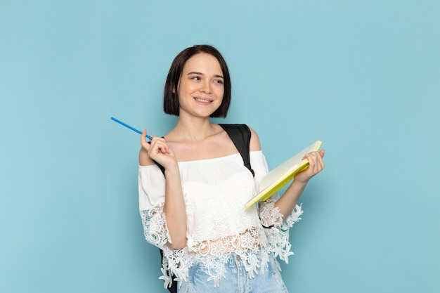 Giovane studentessa di vista frontale in blue jeans della camicia bianca e borsa nera che annota le note sulla scuola dell'università della studentessa dello spazio blu