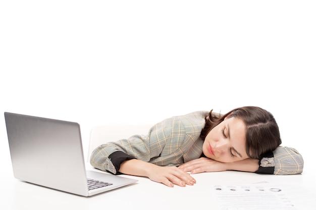 Giovane studentessa o lavoratore di ufficio oberati di lavoro che dorme sulla scrivania davanti al computer portatile mentre si prepara per gli esami o il progetto