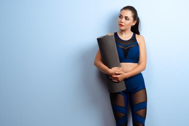 Giovane stuoia esile di forma fisica di yoga della tenuta della donna in sue mani