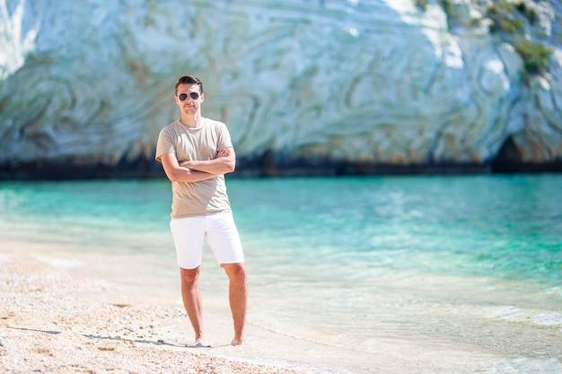Giovane sulla spiaggia tropicale bianca