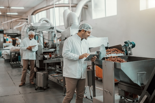 Giovane supervisore caucasico che valuta la qualità del cibo nella pianta alimentare mentre si tiene la compressa. l'uomo è vestito in uniforme bianca e con retina per capelli.