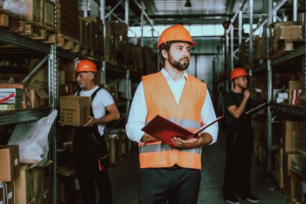 Giovane supervisore in elmetto protettivo che cammina attraverso il magazzino