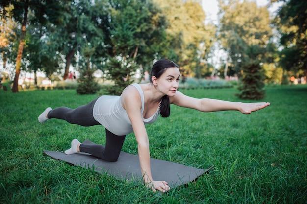 Giovane supporto della donna incinta sulle ginocchia ed esercitarsi sul compagno di yoga in parco. allunga le gambe e le braccia. donna concentrata e seria non vede l'ora.