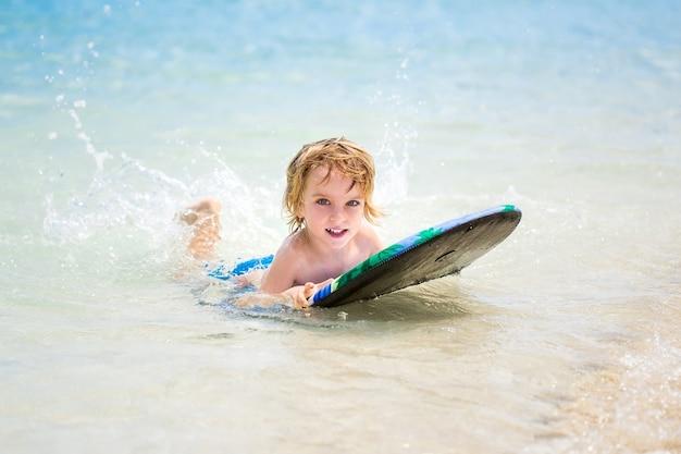 Giovane surfista, felice ragazzo nell'oceano sulla tavola da surf