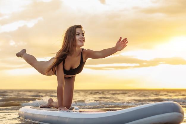 Giovane surfista sexy della donna che fa yoga sul suo bordo del sup sul tramonto.
