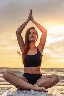Giovane surfista sexy della donna che medita su suo bordo del sup sul tramonto.