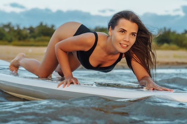 Giovane surfista sexy della donna che si trova sul suo bordo del sup che guarda al tramonto.