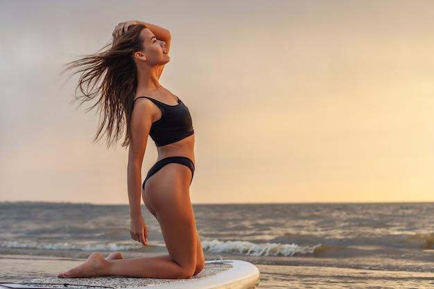Giovane surfista sexy della donna che sta sul suo bordo del sup che guarda al tramonto.