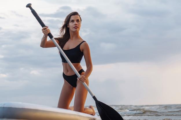 Giovane surfista sexy della donna che sta sul suo bordo del sup con una pagaia.