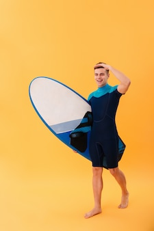 Giovane surfista sorridente che cammina con la tavola da surf e distogliere lo sguardo