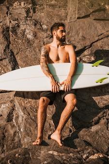 Giovane tavola da surf barbuta della tenuta dell'uomo vicino alle pietre