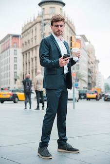 Giovane tazza di caffè della tenuta dell'uomo d'affari che sta sulla via che esamina telefono cellulare