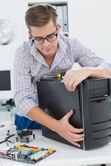 Giovane tecnico che lavora al computer rotto