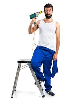 Giovane tecnico elettrico con un trapano che fa il gesto suicida