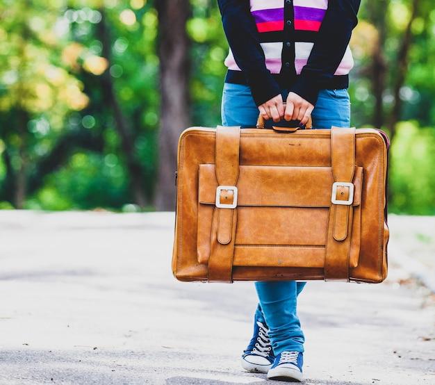 Giovane teenager girt con la valigia in un parco