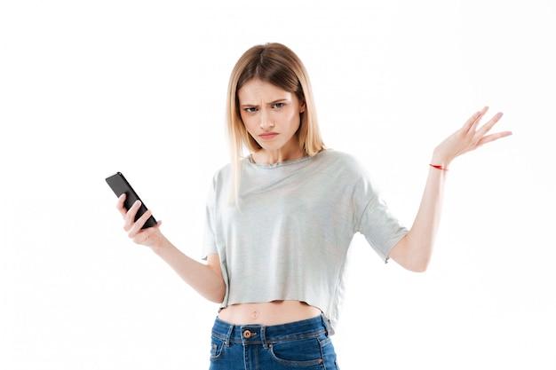 Giovane telefono cellulare confuso della tenuta della giovane donna e scrollare le spalle le spalle