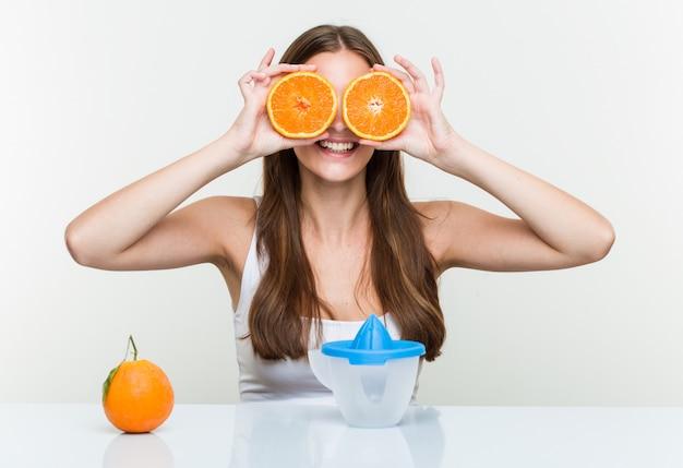 Giovane tenuta caucasica della donna che produce un succo d'arancia