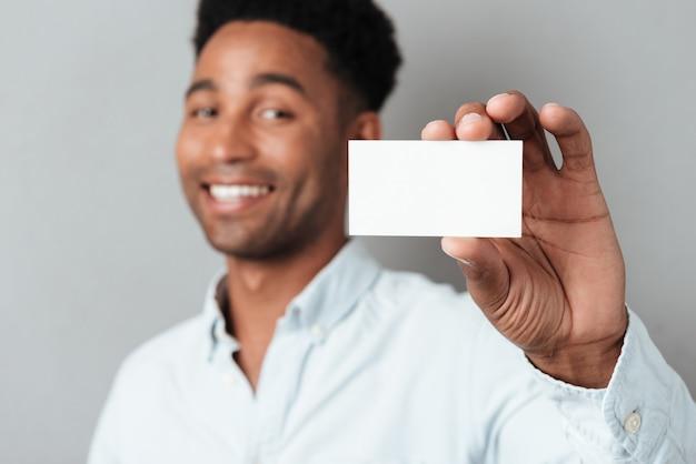 Giovane tipo afroamericano sorridente che mostra biglietto da visita in bianco