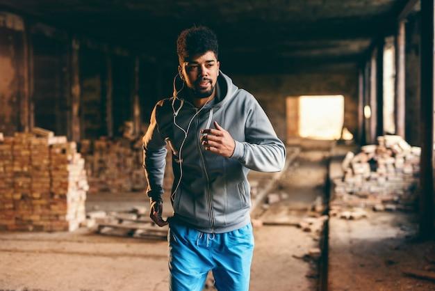 Giovane tipo afroamericano sportivo in abiti sportivi e con le cuffie che corrono nella vecchia fabbrica di mattoni.