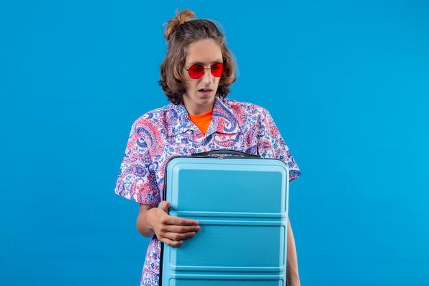 Giovane tipo bello che indossa gli occhiali da sole rossi che tengono la valigia di viaggio che sembra condizione confusa