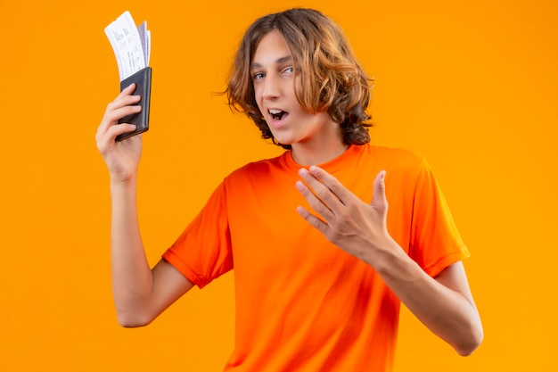 Giovane tipo bello in maglietta arancione che tiene i biglietti di aria che sembrano fondo arancio controllante positivo e felice sicuro