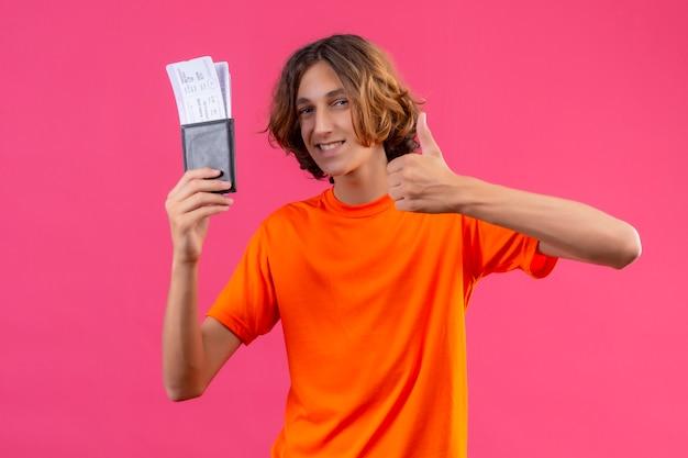 Giovane tipo bello in maglietta arancione che tiene i biglietti di aria che sembrano i pollici di mostra sicuri su che sorridono allegramente stando