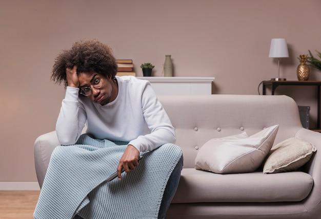Giovane triste sul divano con telecomando